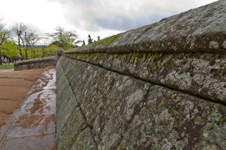 Old stone wall with moss growing out of it in a cloudy day
