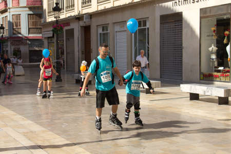 MALAGA, SPAIN - JUNE 19: Father skates with his son at the 6th Skate Day race on June 19, 2011 in Malaga, Spain