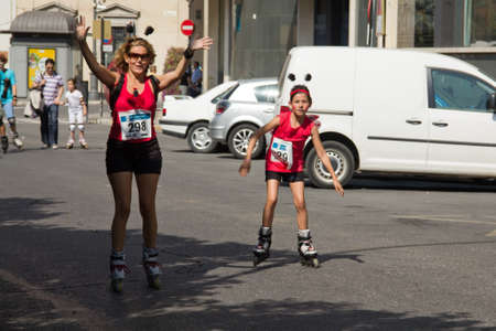MALAGA, SPAIN - JUNE 19: Mother skates with her daughter at the 6th Skate Day race on June 19, 2011 in Malaga, Spain