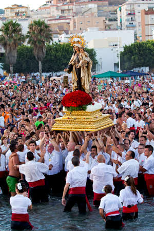 MALAGA, SPAIN - JULY 16: Unidentified local worshippers lift a religious image at the beach during the Virgen del Carmen festival on July 16, 2011 in Malaga, Spain. The Virgen del Carmen is the patron saint and protector of fishermen and sailors