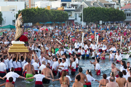 MALAGA, SPAIN - JULY 16: Unidentified local worshipers lift a religious image at the beach during the Virgen del Carmen festival on July 16, 2011 in Malaga, Spain. The Virgen del Carmen is the patron saint and protector of fishermen and sailors