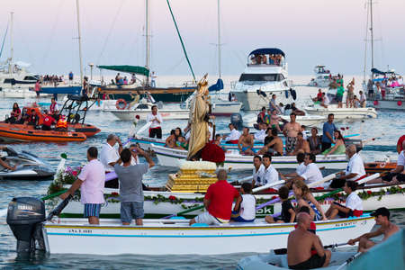 MALAGA, SPAIN - JULY 16: Unidentified local worshipers carry a religious image on a boat during the Virgen del Carmen festival on July 16, 2011 in Malaga, Spain. The Virgen del Carmen is the patron saint and protector of fishermen and sailors