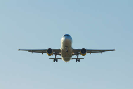 Airplane landing with a blue sky Stock Photo