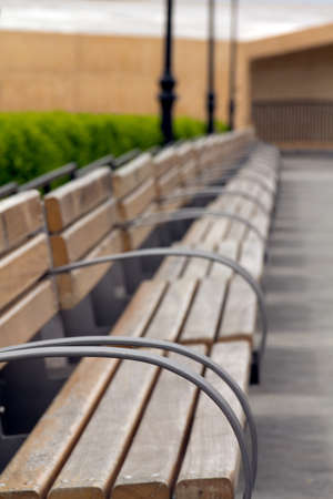 Metallic and wooden benches in a row, shallow depth of field selective focus on the first
