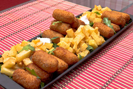 Croquettes and fries on black platter with arugula leaves Stock Photo