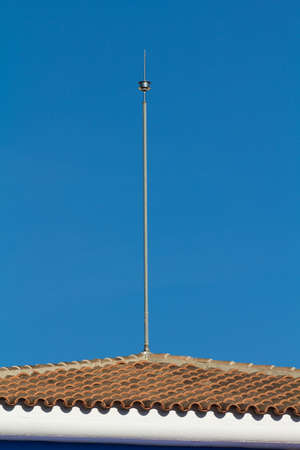 conductor electricity: Lightning conductor on a tile roof with a blue sky Stock Photo
