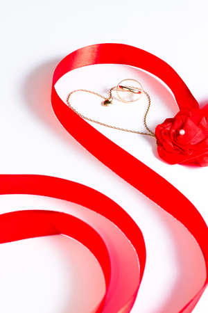Golden wedding bands and chain with heart surrounded by red ribbon with rose bow on white background