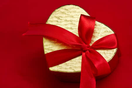 Golden box in heart shape with red ribbon on red background photo
