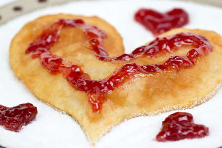 Fried flat cake in form of heart with strawberry jam over sugar photo