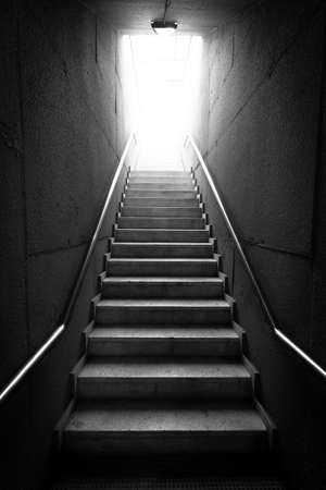 Black and white image of a dark hallway staircase