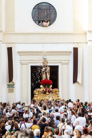 MALAGA, SPAIN - JULY 16: Unidentified local worshippers lift a religious image out of the church during the Virgen del Carmen procession on July 16, 2012 in Malaga, Spain. The Virgen del Carmen is the patron saint and protector of fishermen and sailor