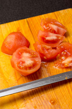 Peeled and sliced tomatoes on a wood cutting board