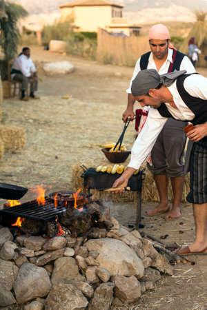 reenacting: MALAGA, SPAIN - OCTOBER 13: Unidentified men cooking chestnuts at Pasion Bandolera reenactment of 1840 Editorial