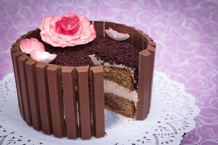 Chocolate cake with fondant rose with a slice missing