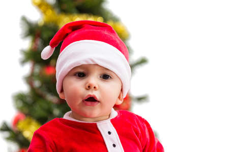 Baby wearing a red and white Christmas Santa hat and suit, isolated on a white  photo