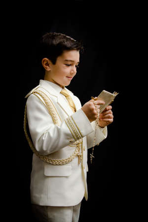 A young boy with rosary and prayer book celebrating his First Holy Communion