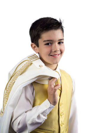 A young boy in his First Holy Communion holding his jacket