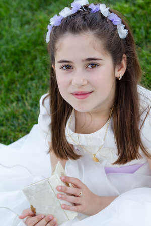 A young girl with prayer book celebrating her First Holy Communion