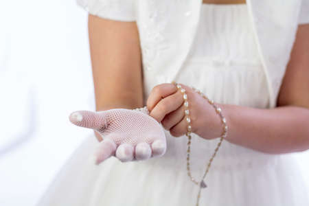 A young girl with rosary putting on her gloves for her First Holy Communion photo
