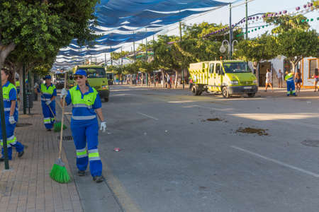 squad: MALAGA, SPAIN - AUGUST 21, 2014: Squad cleaning the streets at the august fair of Malaga