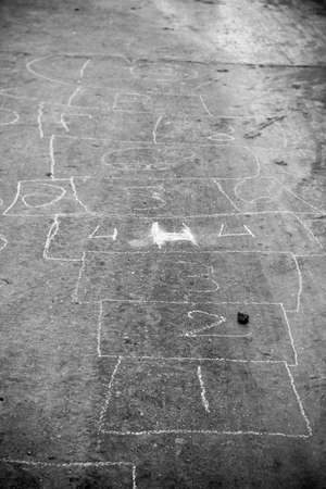Hopscotch game drawn out on a road surface with white crayon - shallow depth of field photo