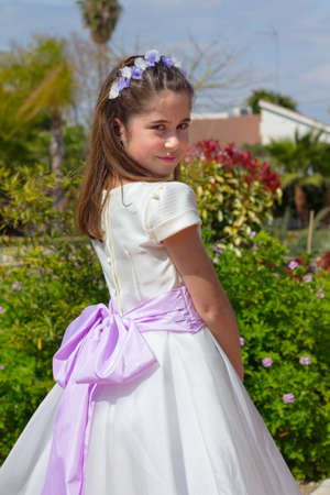 A young girl smiling and celebrating her First Holy Communion Stock Photo