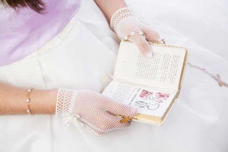 holiday prayer book: Ni�a leyendo un libro de oraciones con el texto espa�ol en su primera comuni�n santa Foto de archivo