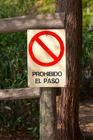 Prohibition sign in spanish on a wooden post in the countryside. Prohibido el paso, Forbidden pass