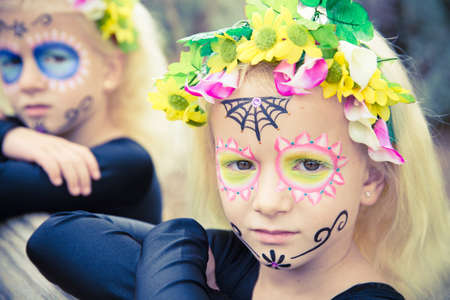 blond girl: Little girls with black clothing and sugar skull makeup looking seriously at camera Stock Photo