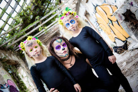 twin house: Woman and twin sisters with sugar skull makeup in abandoned house