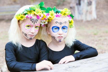 niñas gemelas: Maquillaje de Halloween. Foto de niñas gemelas con ropa de color negro sentado frente a una mesa al aire libre Foto de archivo