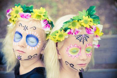 niñas gemelas: Muchachas gemelas con los ojos cerrados en traje de halloween al aire libre