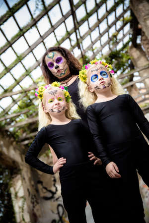 day of the dead: Woman and twin sisters with halloween makeup in abandoned house