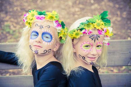 niñas gemelas: Lindas niñas gemelas sonrientes con el maquillaje del cráneo del azúcar en un banco de madera