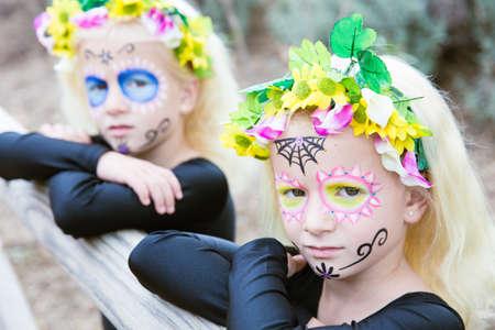niñas gemelas: Foto de niñas gemelas con maquillaje del cráneo del azúcar apoyado en una valla de madera