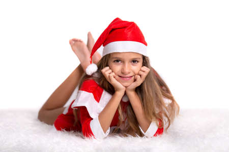 the laying: Cute girl wearing a red and white Christmas Santa hat and suit lying on a furry white carpet