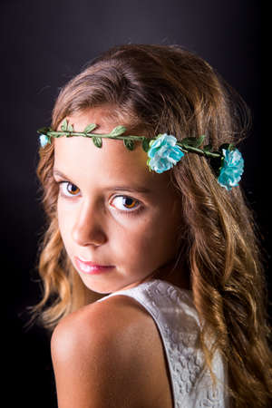 sober: Closeup of a young girl with long hair and flower tiara posing with a sober look on a black background