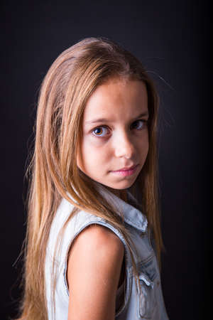 sober: Young girl with long hair and denim jacket posing with a sober look on a black background Stock Photo