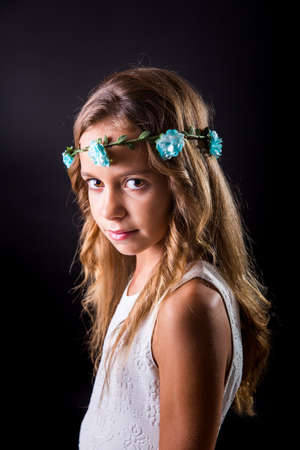 sober: Young girl with long hair and flower tiara posing with a sober look on a black background