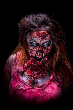 Portrait of a scary zombie girl staring with bloody makeup and latex prosthesis.