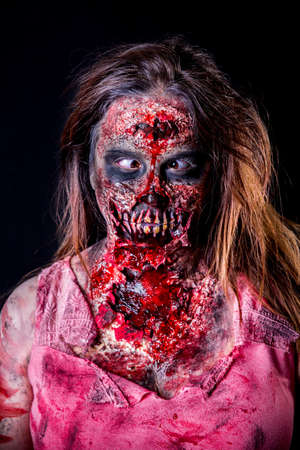 Portrait of zombie girl with crossed eyed and bloody makeup with latex prosthesis.