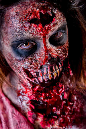 Closeup of zombie girl staring with bloody makeup and latex prosthesis. Stock Photo
