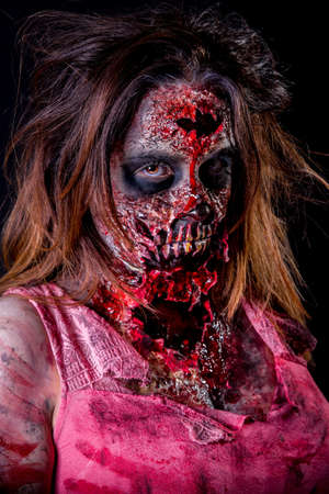 Portrait of zombie girl with bloody makeup and latex prosthesis.
