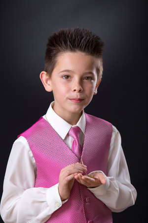 Young boy celebrating his First Holy Communion holding his medals and looking at camera on a black background. Stock Photo