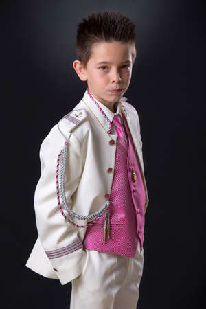 Young boy standing in his First Holy Communion looking at camera seriously on a black background. Stock Photo