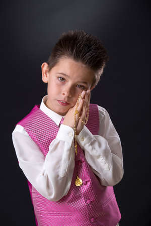 Young boy celebrating his First Holy Communion holding his rosary and looking at camera on a black background.