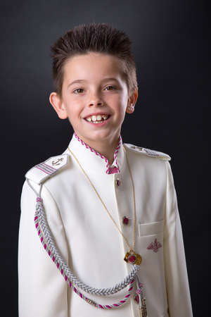 Young boy celebrating his First Holy Communion looking at camera on a black background. Stock Photo