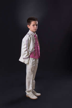 Young boy in his First Holy Communion looking at camera and standing with a serious expression on a black background.