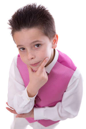 Young boy holding his chin and looking at camera celebrating his First Holy Communion on a white background. High angle shot.