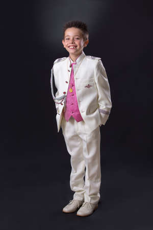Young boy celebrating his First Holy Communion looking at camera and standing on a black background.